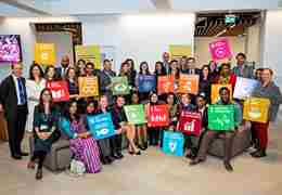 ACU staff members sit and stand together holding up signs showing the SDG icons