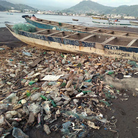 Plastic waste on shore with boat