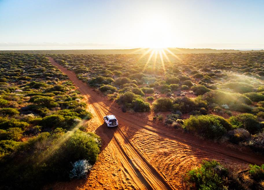 A white 4x4 drives along a remote dirt road at golden hour. Credit Francesco Ricca Iacomino