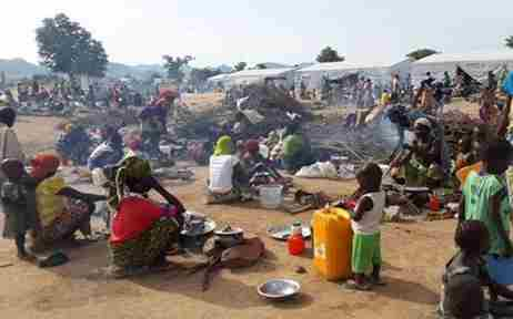 Internally displaced people sat and stood in a refugee camp