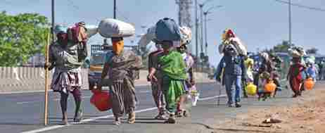 Group of migrants walking and carrying sacks above their heads