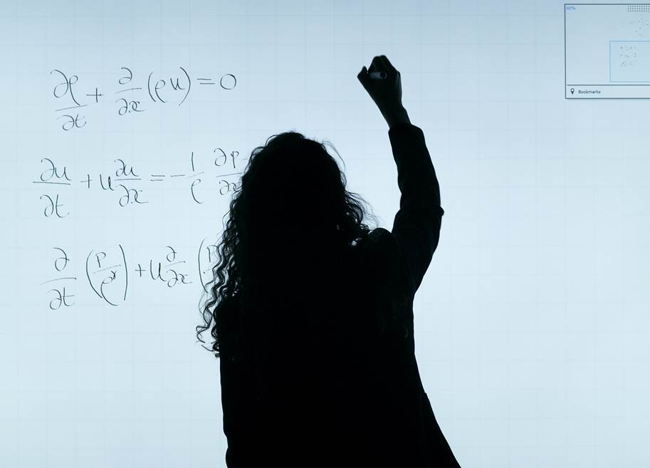 Silhouette of woman writing equations