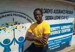 ACU Summer School student stood in front of community library in Sierra Leone