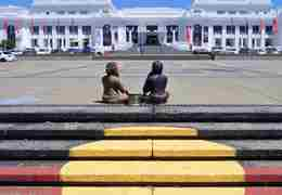 Two aboriginal men sit in in front of a white building at the top of steps painted with a yellow circle on red